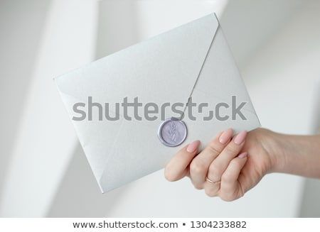 close up photo of female hands holding a silver invitation envelope with a wax seal a gift certific stock photo © vbdpua