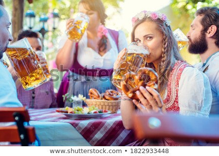 Woman in Tracht looking into camera while drinking a mass of beer Stock photo © Kzenon