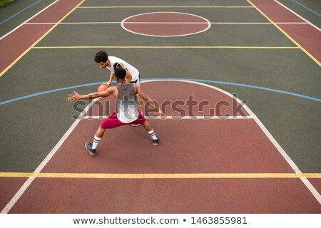 Young sportsman carrying ball while trying to throw it over his rival Stock photo © pressmaster