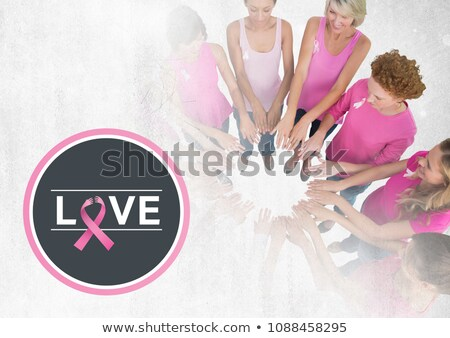 Love text and pink ribbons with breast cancer awareness women putting hands together Stock photo © wavebreak_media