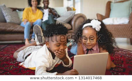 Front view of cute African American sibling lying on floor and using digital tablet in a comfortable Stock photo © wavebreak_media