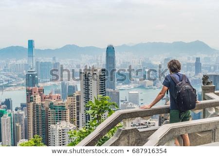 Young man traveler at the peak of Victoria against the backdrop of Hong Kong Stock photo © galitskaya