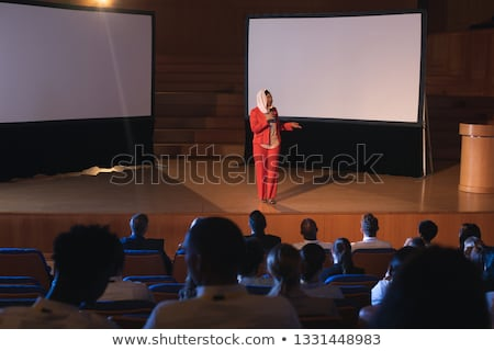 Front view of young Asian businesswoman standing at podium on stage in auditorium  while looking at  Stock photo © wavebreak_media