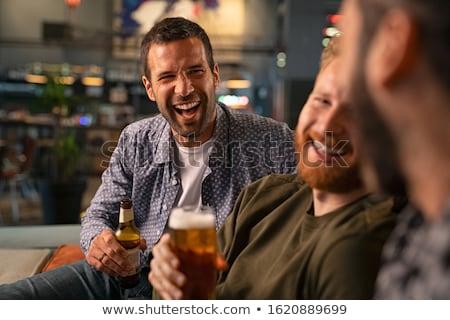 Grupo feliz amigos botellas cerveza sesión Foto stock © pressmaster