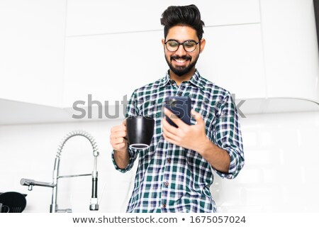 happy indian man holding coffee table at home Stock photo © dolgachov