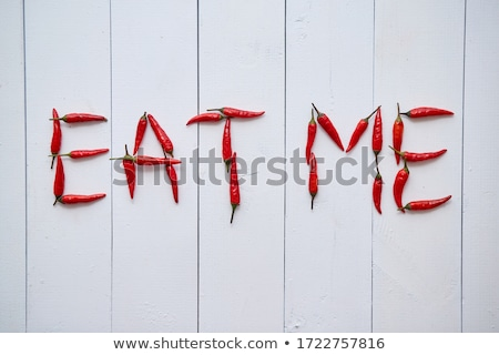 A word EAT ME formed with small red chilli peppers. Placed on white wooden table Stock photo © dash