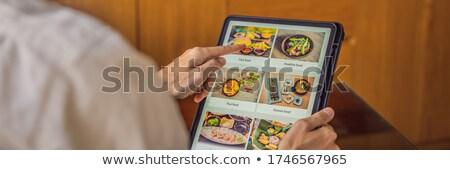 man orders food for lunch online using Tablet BANNER, LONG FORMAT Stock photo © galitskaya