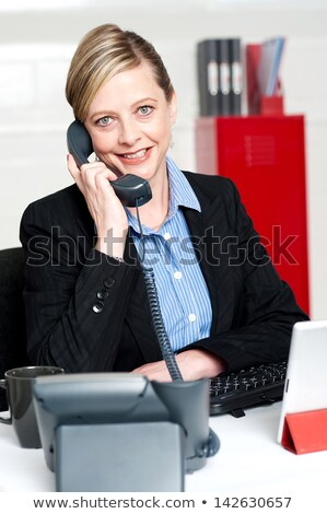 Corporate lady posing with telephone receiver Stock photo © stockyimages