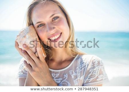 Donna ascolto shell spiaggia cielo acqua Foto d'archivio © wavebreak_media