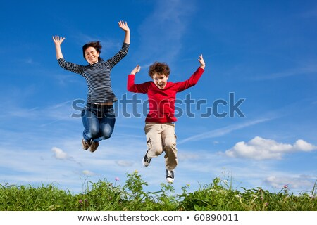 mother and son jumping in meadow stock photo © jasminko