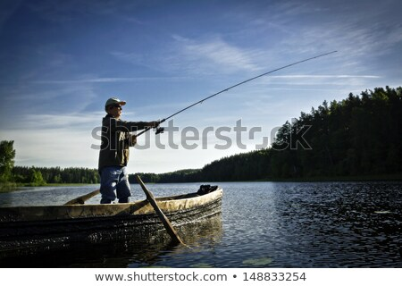 Young angler boat fisherman with rod and reel Stock photo © lunamarina
