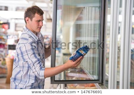 férfi · áruház · áll · mélyhűtő · néz · kedvenc - stock fotó © hasloo