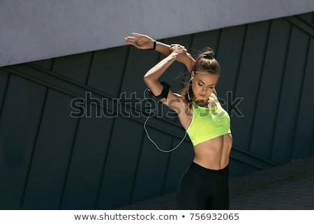 Stock photo: Young sportswoman stretching before a training