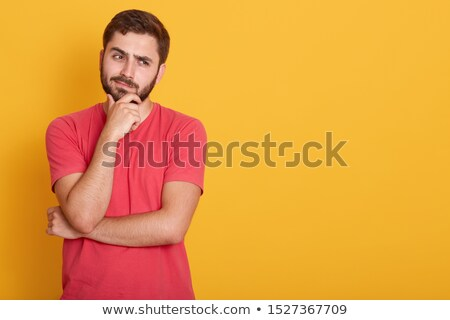 Serious muscular man in red t-shirt standing over gray background Stock photo © deandrobot