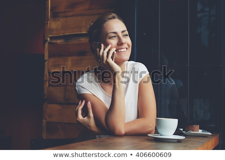 young woman talking on the cell phone and reading a newspaper in stock photo © vlad_star
