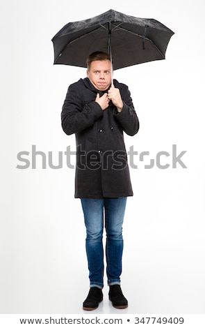 Amusing young man standing and feeling cold under umbrella  Stock photo © deandrobot