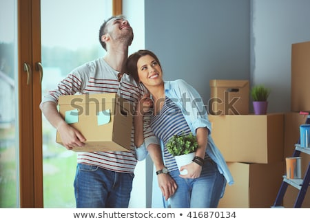 Young pretty couple unpacking in new flat Stock photo © deandrobot