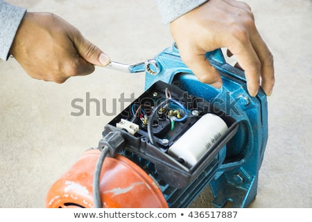 Electric motor  and man working equipment repair on cement floor background.Background motor or equi stock photo © Bigbubblebee99