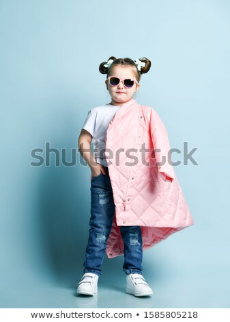 Cheerful little girl in torn jeans standing and smiling Stock photo © deandrobot
