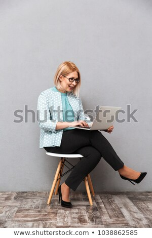 Happy mature woman sitting and posing isolated over grey wall Stock photo © deandrobot