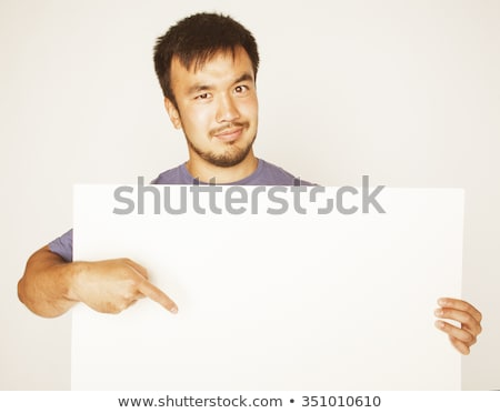 pretty cool asian man holding empty white plate smiling stock photo © iordani