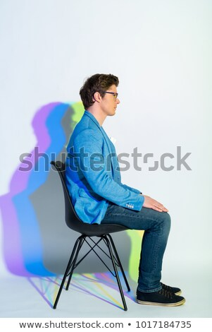 Full-length portrait of young man sitting on chair putting hands Stock photo © deandrobot