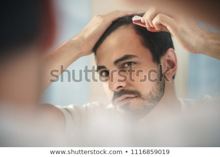 Young Man Applying Lotion For Alopecia And Hair Loss Treatment Stock photo © diego_cervo