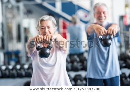 Smiling couple doing weight lifting exercise Stock photo © Kzenon