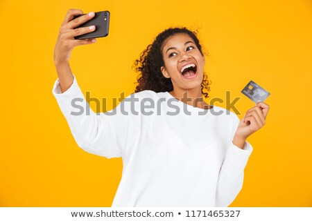 Stock photo: African woman posing isolated over yellow background take a selfie by mobile phone.