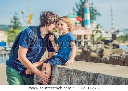 Father and son travelers in the background Dinh Cau lighthouse symbol of the island Phu Quoc, Vietna Stock photo © galitskaya