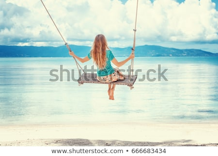 Woman swinging at the tropical beach. stock photo © NeonShot