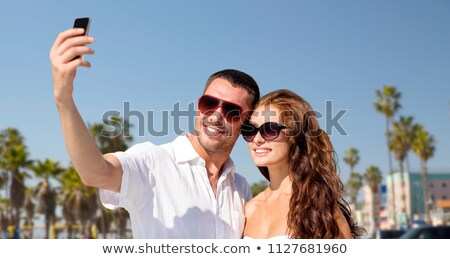couple making selfie by smartphone over beach stock photo © dolgachov