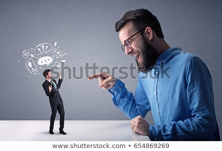 Young businessman fighting with miniature businessman Stock photo © ra2studio