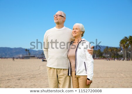 happy senior couple hugging over venice beach Stock photo © dolgachov