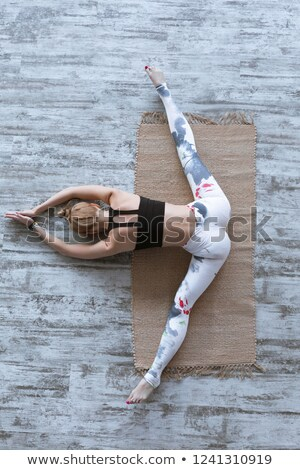 view from above of young beautiful woman stretching at home stock photo © dash