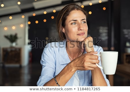 Thoughtful smiling woman sitting in cafeteria. Stock photo © NeonShot