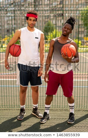 Two young professional multicultural basketball players on playground Stock photo © pressmaster