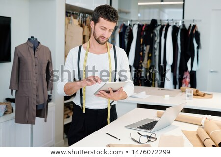 Young man concentrating on networking while scrolling in touchpad Stock photo © pressmaster