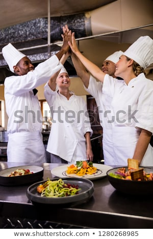 Group of chefs formig hands stack in kitchen at hotel Stock photo © wavebreak_media