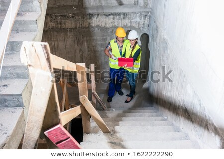 Construction worker and builder inspecting stairs in building shell Stock photo © Kzenon