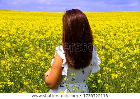 woman in white dress standing by fields of golden canola stock photo © lovleah