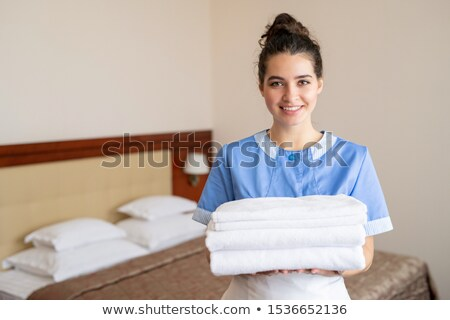 Pretty young smiling chamber maid in uniform holding stack of white clean towels Stock photo © pressmaster