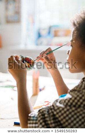 Diligent African pupil painting handmade decorative toy ball for holiday Stock photo © pressmaster
