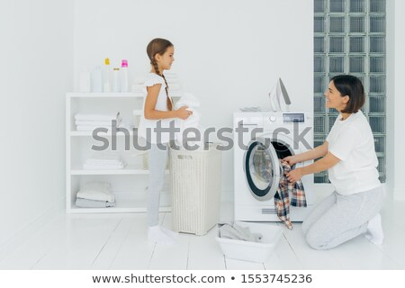 Glad mother and daughter busy doing laundry at home, have happy faces, brunette woman loads washing  Stock photo © vkstudio