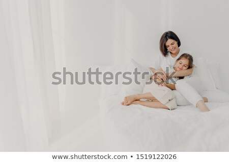 Photo of relaxed young mother embraces daughter with love, pose in pyjamas bare foot, have pleasant  Stock photo © vkstudio