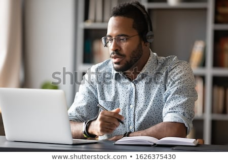 Image of african american man in headphones using laptop compute Stock photo © deandrobot
