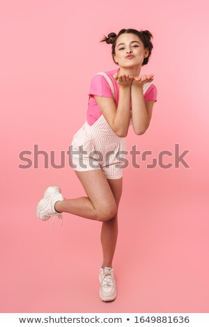 Photo of nice charming girl in overalls posing and sending air kiss Stock photo © deandrobot