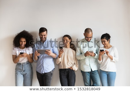 Smart woman using a cellphone as a male colleague watches in the background Stock photo © photography33