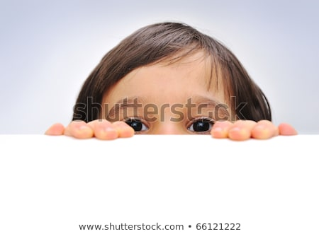 child holding an empty sign over a white background hiding behind stock photo © zurijeta