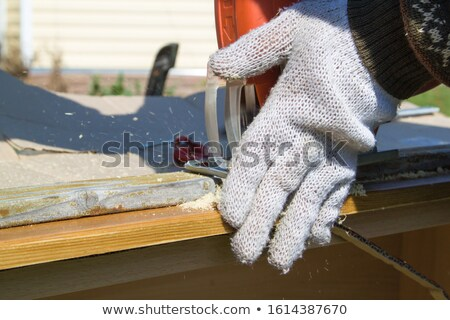 Stock photo: Man using an electric jigsaw to cut a piece of wooden flooring